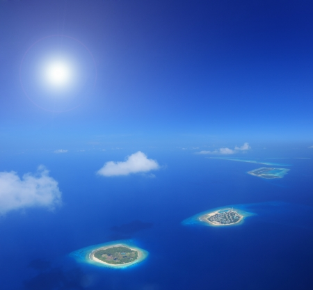 Sun and clouds over islands in Laccadives sea, Maldives, shot with a tilt and shift lens photo