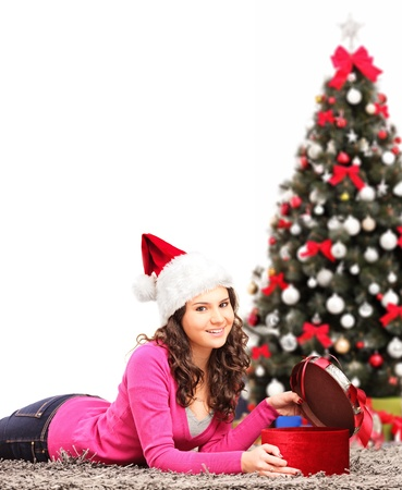 A young female next to a christmas tree, opening a present photo