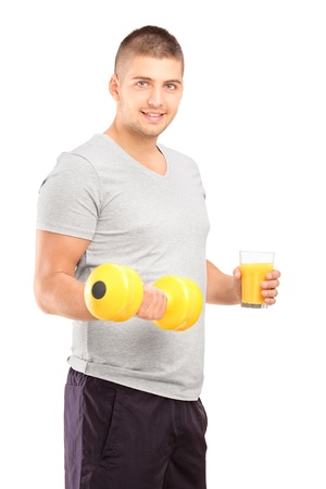 Young man holding a dumbbell and glass of fresh orange juice isolated on white background photo
