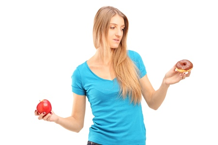 Doubtful woman holding an apple and donut trying to decide which one to eat photo