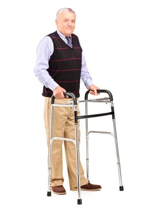 ancianos caminando: Retrato de cuerpo entero de un caballero maduro utilizando un andador aislado sobre fondo blanco Foto de archivo
