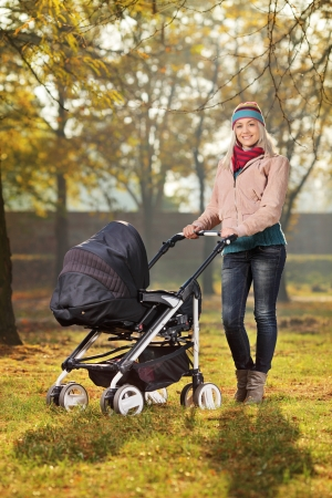 perambulator: A smiling mother posing with a baby stroller in a park in autumn