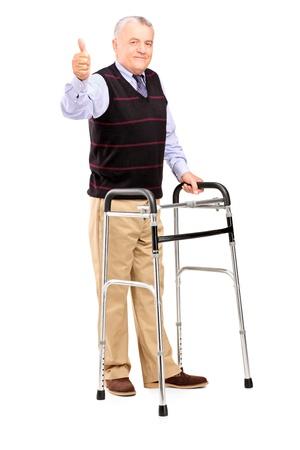 marcheur: Portrait en pied d'un homme mûr à l'aide d'une marchette et de donner un pouce vers le haut isolé sur fond blanc