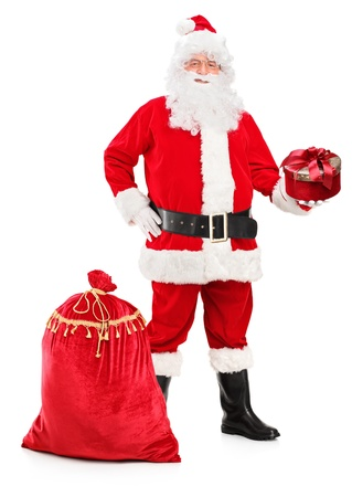 Full length portrait of a Santa Claus holding a gift and bag full of presents next to him isolated on white background Stock Photo - 16547498