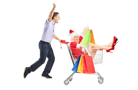 Guy pushing a woman in christmas costume with shopping bags in a push cart isolated on white background  photo