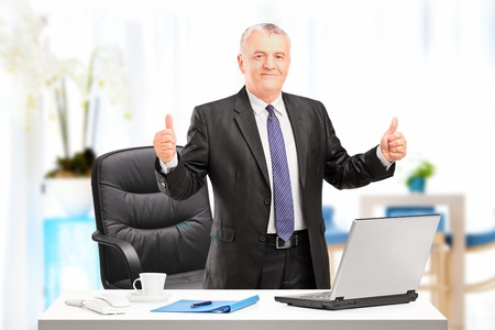 Happy mature businessman standing in his office and giving thumbs up photo