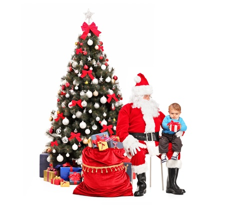 Santa Claus giving a gift to a child in front of decorated christmas tree Stock Photo - 16547503