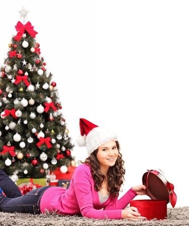 Young female lying down and opening a present, in front of the christmas tree Stock Photo - 16547489