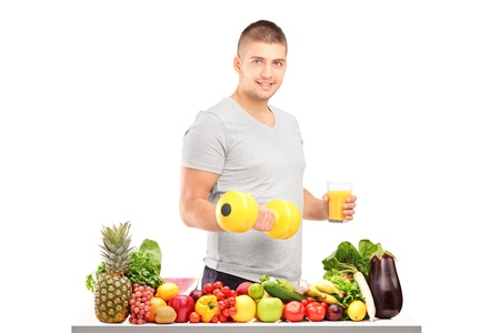 Young guy holding a dumbell and glass of fresh orange juice behind a pile of different fruits isolated on white background photo