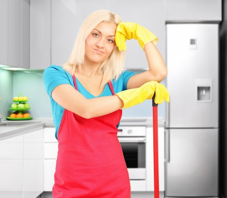 kitchen device: A tired female cleaner resting after cleaning a kitchen