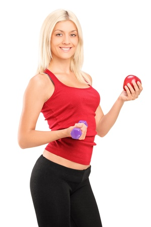Attractive athlete female holding a dumbbell and red apple isolated on white background Stock Photo - 16547556
