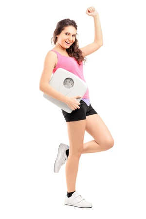 diet concept: Full length portrait of a young happy female holding a weight scale isolated on white background