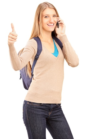 A smiling female student talking on a phone and giving thumb up isolated against white background Stock Photo - 16577921