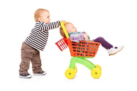 gemelos niÑo y niÑa: Muchacho niño empujando a su hermana gemela en un carrito de juguete aislado sobre fondo blanco Foto de archivo