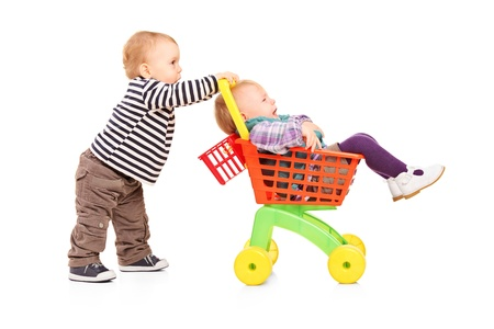 twins: Toddler boy pushing his twin sister in a toy cart isolated on white background