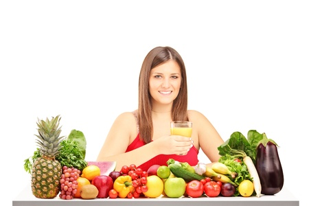 Young female holding a glass of juice and posing behind a pile of different fruits and vegetables isolated on white background photo