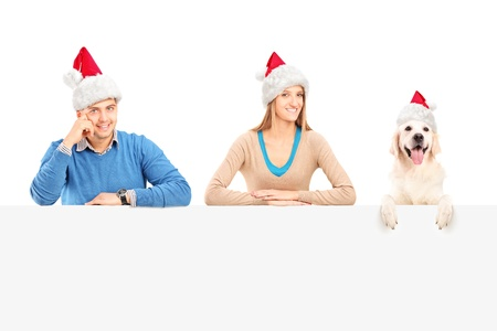Smiling couple and dog with santa claus hats posing behind a blank panel photo