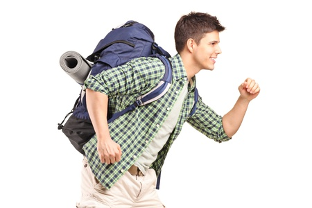 A young hiker with backpack running isolated on white background photo