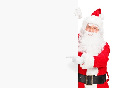 Santa claus posing next to a blank billboard and pointing isolated on white background Stock Photo - 16639728
