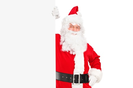 A smiling Santa Claus posing next to a billboard isolated on white background Stock Photo - 16639726