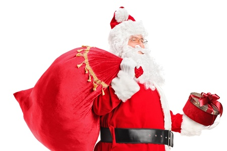 A Santa Claus carrying a bag full of gifts on his back isolated on white background Stock Photo - 16639723