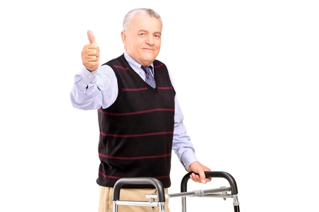 A mature gentleman using a walker and giving a thumb up isolated on white background Stock Photo - 16639743