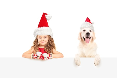 A small girl and dog wearing santa hats and posing behind a blank panel photo