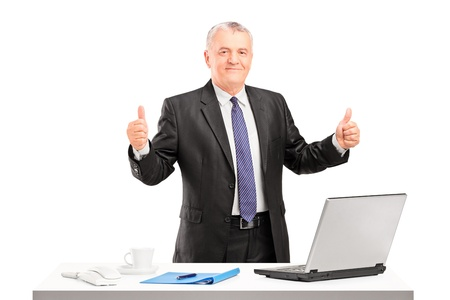 approval: Happy mature businessman standing and giving thumbs up isolated on white background