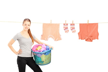 clothes pegs: Smiling woman holding a laundry basket and a laundry line with clothes isolated on white background Stock Photo