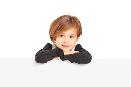 A small girl posing on a blank panel isolated on white background Stock Photo - 16660787