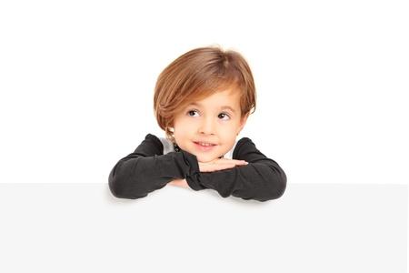 niños pensando: Una niña posando en un panel en blanco aislado en fondo blanco Foto de archivo