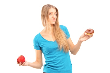 Young doubtful female holding a red apple and donut trying to decide which one to eat photo