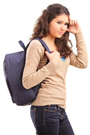 A sad female teenager with a school bag on her back posing isolated on white background photo