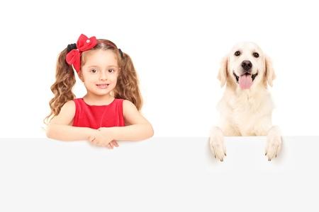 A small girl and Labrador retriever posing behind a blank panel Stock Photo - 16732379