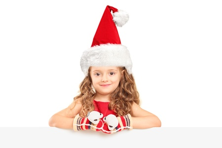 A small girl with santa hat posing behind a blank panel Stock Photo - 16732380