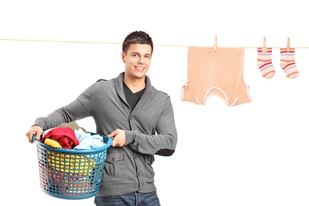 clothes peg: Smiling guy holding a laundry basket and a laundry line with clothes isolated on white background