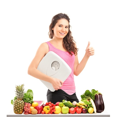 Young female holding a weight scale and giving a thumb up behind a pile of different food isolated on white background Stock Photo - 16732383