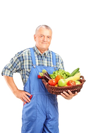 Mature farmer holding a basket full of fresh vegetables isolated against white background photo