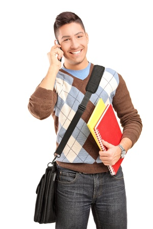 A smiling male student with shoulder bag and books talking on a cell phone isolated against white background Stock Photo - 16757239