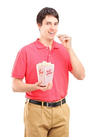 dessert stand: Young smiling man eating popcorn isolated on white background