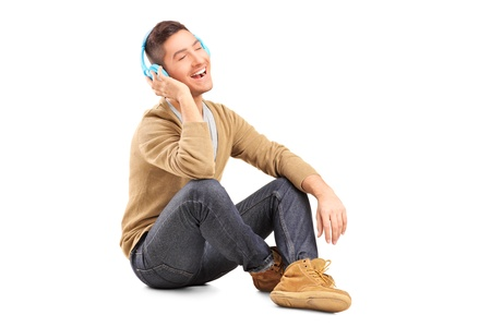 A young guy sitting on a floor and listening music on headphones isolated on white background photo