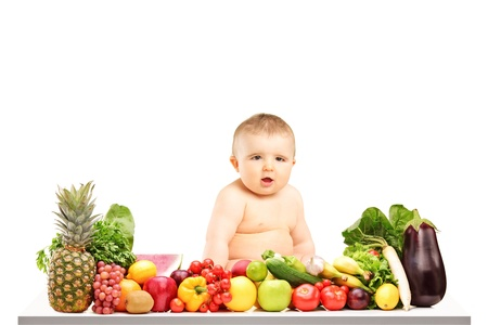 A 9 months old baby sitting on a table full of different fruits and vegetables isolated against white background photo