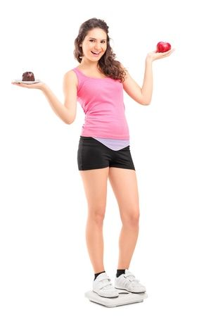 A smiling female on a weight scale holding a red apple and chocolate cake isolated on white background Stock Photo - 16810806