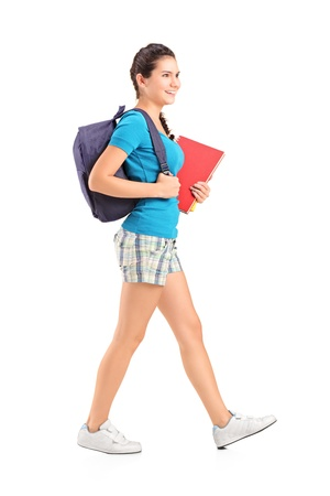 Full length portrait of a female student with backpack walking and holding book isolated on white background photo