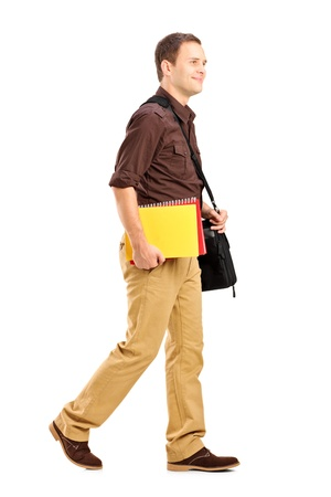 Full length portrait of a male student with shoulder bag holding books and walking isolated on white background