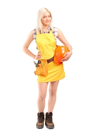 Full length portrait of a smiling female worker with a tool belt holding helmet isolated on white background photo