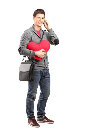 Full length portrait of a smiling student holding a red heart and talking on a phone isolated on white background Stock Photo - 16810479