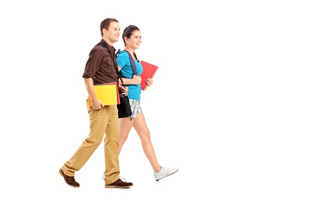 Full length portrait of a two students holding books and walking isolated on white background photo