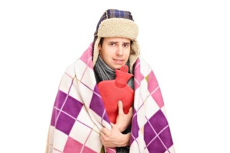 w�rmflasche: Kranker Mann mit Decke abgedeckt, die eine W�rmflasche vor wei�em Hintergrund isoliert Lizenzfreie Bilder