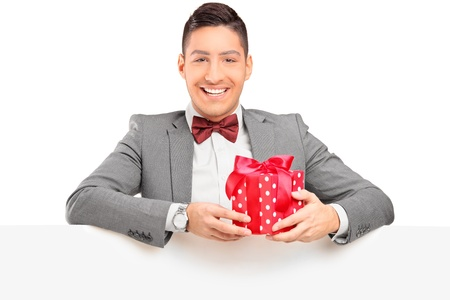 A handsome guy with bow tie holding a gift behind a blank panel photo